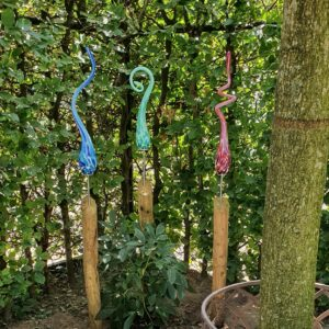 Kleurrijke tuinprikkers op houten palen